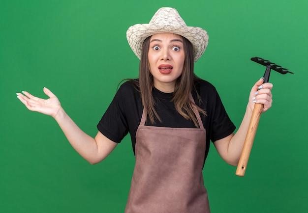 갈퀴를 들고 정원용 모자를 쓰고 복사 공간이 있는 녹색 벽에 격리된 채로 손을 벌리고 있는 불안한 백인 여성 정원사