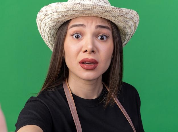 Anxious pretty caucasian female gardener wearing gardening hat looking at camera on green