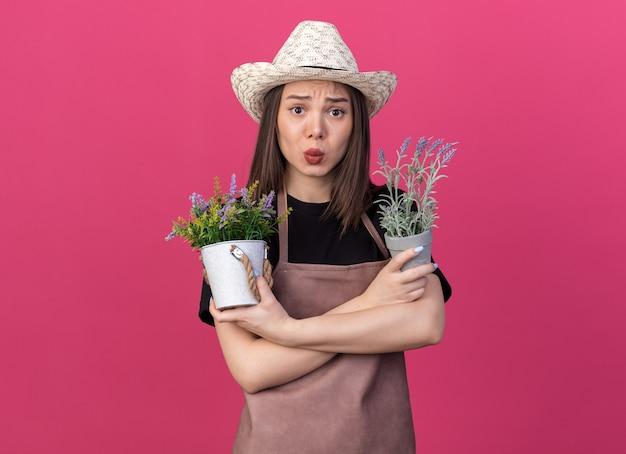 ガーデニングの帽子をかぶって気になるかなり白人女性の庭師は、コピースペースでピンクの壁に分離された植木鉢を保持している腕を組んで立っています