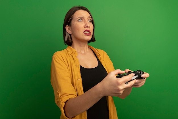 Anxious pretty caucasian woman holds game controller and looks at side isolated