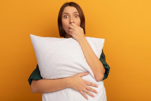 気になるかなり白人女性が枕を持ってオレンジ色の爪を噛む
