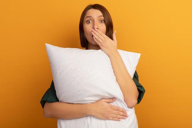 Обеспокоенная симпатичная кавказская женщина держит подушку и кладет руку на апельсин