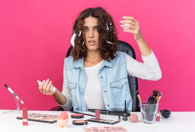 Тревожная симпатичная кавказская женщина сидит за столом с инструментами для макияжа и наносит мусс для волос