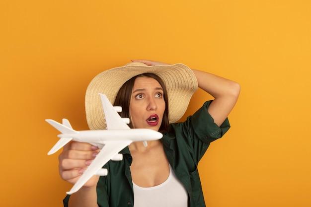 ビーチ帽子をかぶった気になるかなり白人女性はオレンジ色の側面を見て模型飛行機を保持します