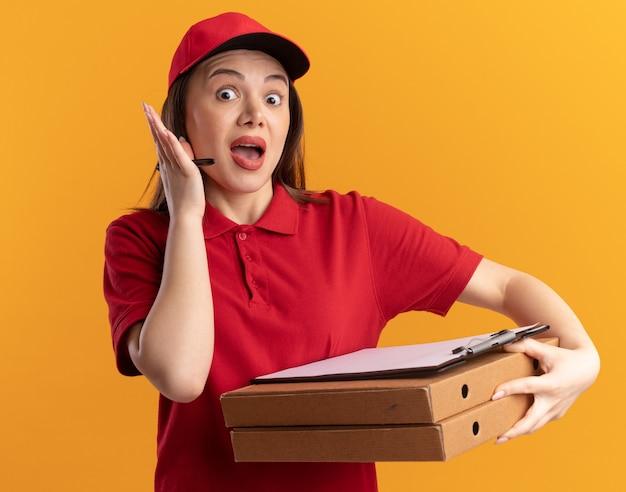 제복을 입은 불안한 예쁜 배달 여자는 오렌지 피자 상자에 마커와 클립 보드를 보유하고 있습니다.