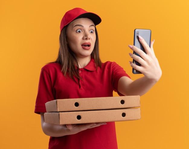 제복을 입은 불안한 예쁜 배달 여자가 피자 상자를 보유하고 오렌지에 전화를 본다.