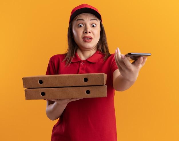 제복을 입은 불안 예쁜 배달 여자는 오렌지에 피자 상자와 전화를 보유하고