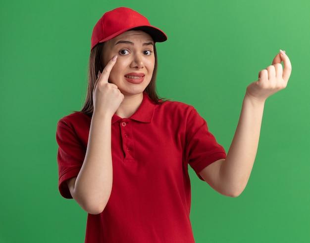 Обеспокоенная симпатичная доставщица в униформе кладет палец на веко и делает вид, что держит что-то на зеленом