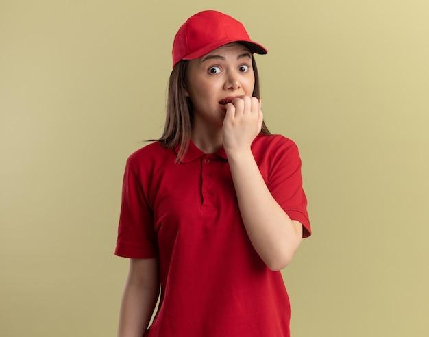 Una donna di consegna graziosa ansiosa in uniforme morde le unghie isolate sulla parete verde oliva con lo spazio della copia