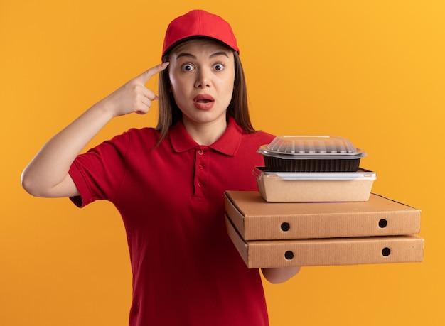 Donna graziosa ansiosa di consegna in uniforme punti alla testa e tiene i pacchetti di cibo di carta sulle scatole della pizza sull'arancia