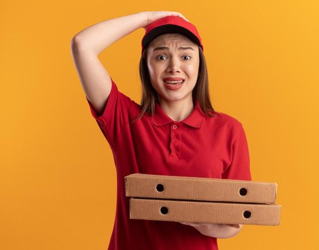 Una graziosa donna delle consegne ansiosa in uniforme mette la mano sulla testa e tiene le scatole della pizza isolate sulla parete arancione con lo spazio della copia