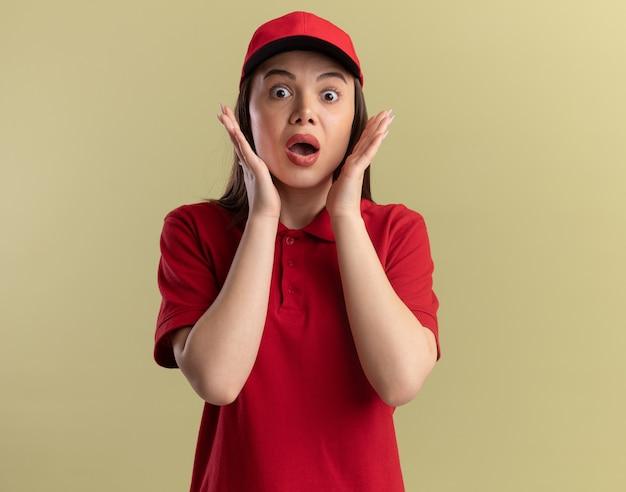 Una bella donna di consegna ansiosa in uniforme mette le mani sul viso isolato sul muro verde oliva con spazio per le copie
