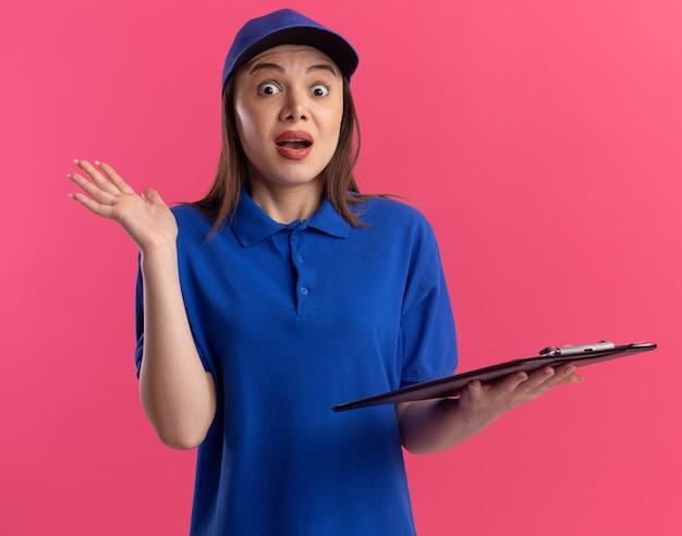 Ansiosa donna di consegna carina in uniforme sta con la mano alzata
