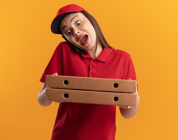 Una bella donna delle consegne ansiosa in uniforme parla al telefono e tiene scatole per pizza