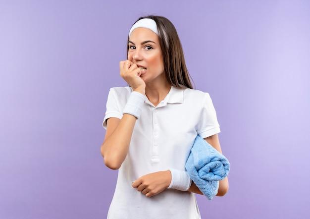 머리띠와 수건을 들고 보라색 벽에 고립 된 그녀의 손가락을 물고 팔찌를 착용하는 불안 꽤 스포티 한 소녀