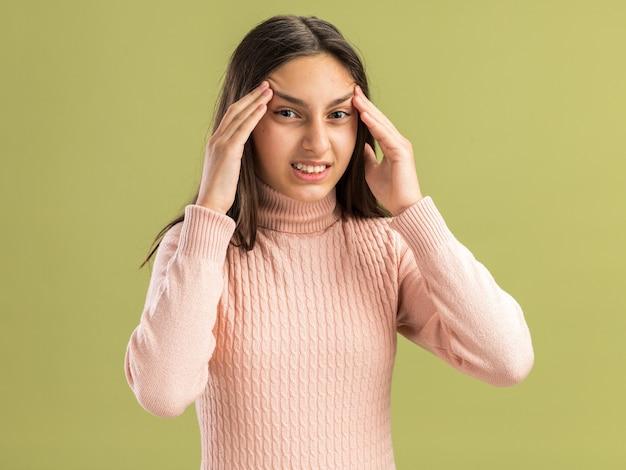 Обеспокоенная симпатичная девочка-подросток, смотрящая вперед, поднимает брови с руками, изолированными на оливково-зеленой стене с копией пространства