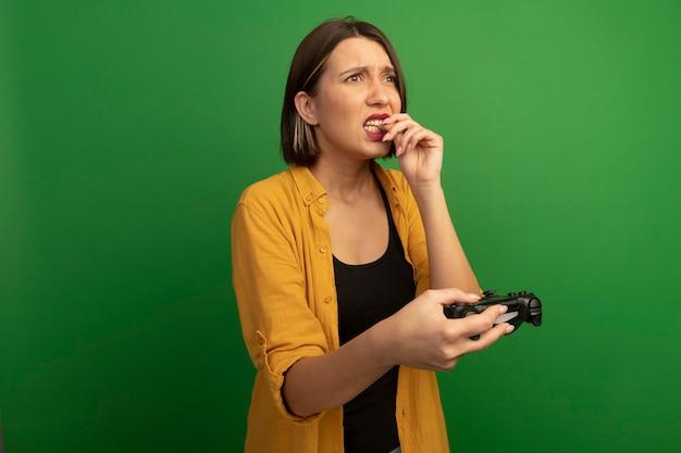 Ansiosa donna graziosa morde il chiodo e tiene il controller guardando il lato isolato sulla parete verde