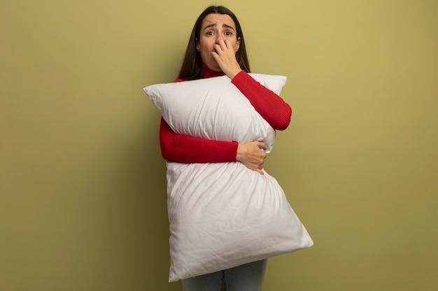 気になるきれいな女性が爪を噛み、オリーブグリーンの壁に分離された枕を保持します。