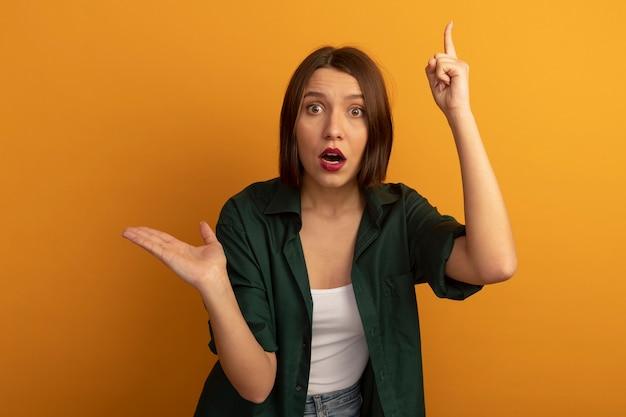 La donna graziosa ansiosa tiene la mano aperta e indica in alto isolato sulla parete arancione