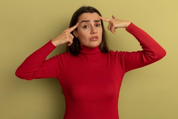 La donna graziosa ansiosa mette le dita sulle tempie isolate sulla parete verde oliva