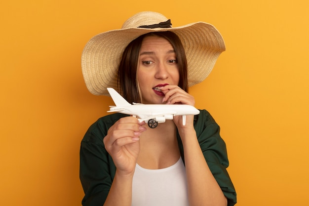 Anxious pretty woman with beach hat bites nails holding and looking at model plane isolated on orange wall