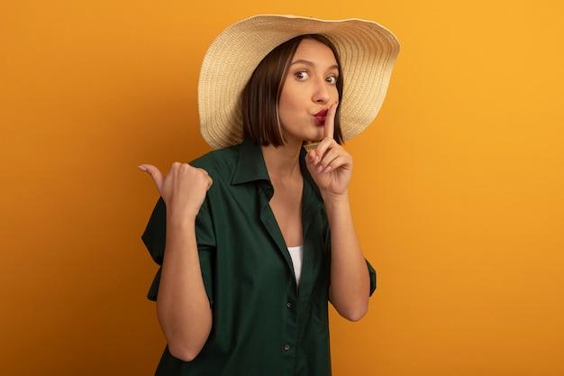沈黙のジェスチャーをしているビーチ帽子とオレンジ色の壁で隔離の側を指す気になるきれいな女性