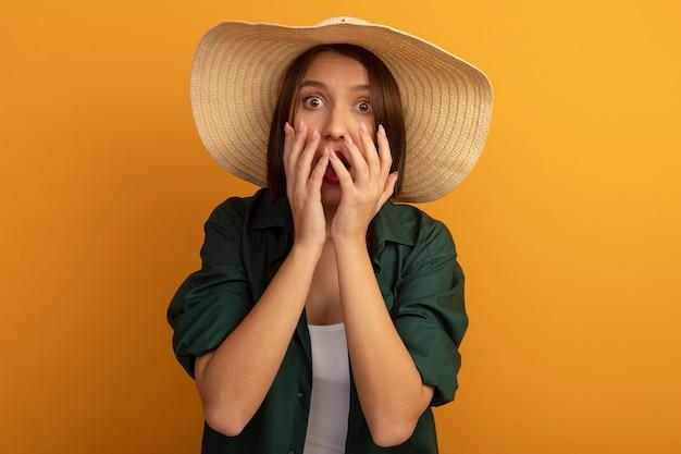 ビーチ帽子をかぶった気になるきれいな女性は、オレンジ色の壁で隔離の口の近くに手を保持します。