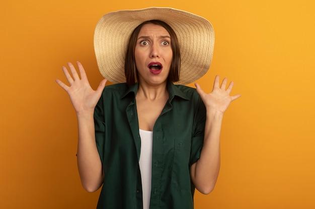 ビーチ帽子をかぶった気になるきれいな女性は、オレンジ色の壁で隔離の上げられた手で立っています