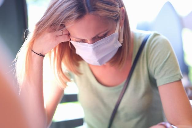 Anxious sad woman in medical protective mask sits at table