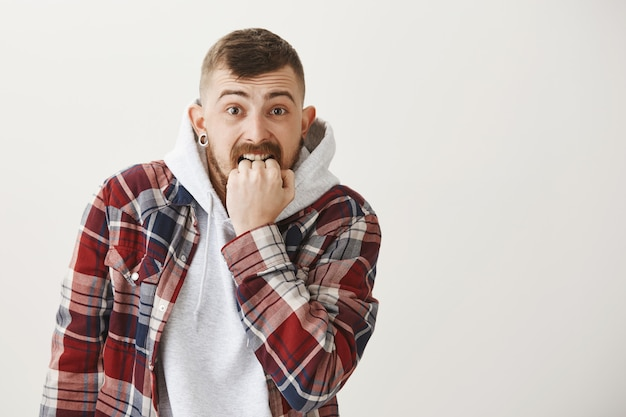 Ragazzo di hipster ansioso e spaventato che morde il pugno preoccupato