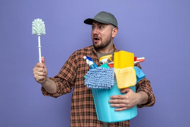 Uomo ansioso delle pulizie slavo che tiene in mano attrezzature per la pulizia e scopino per wc