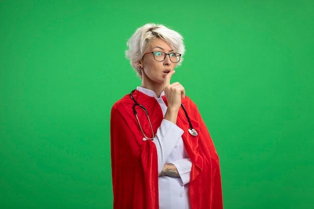 La donna ansiosa del supereroe slavo in uniforme del medico con il mantello rosso e lo stetoscopio in vetri ottici mette il dito sulla bocca isolata sulla parete verde con lo spazio della copia