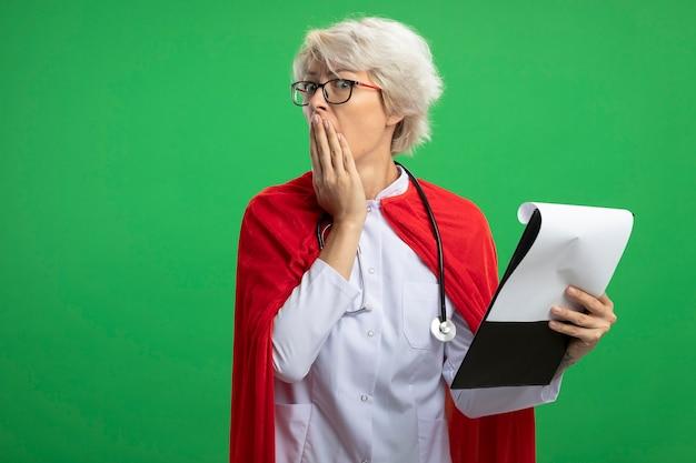 赤いマントと光学ガラスの聴診器で医者の制服を着た気になるスラブのスーパーヒーローの女性は、口に手を置き、コピースペースで緑の壁に隔離されたクリップボードを保持します
