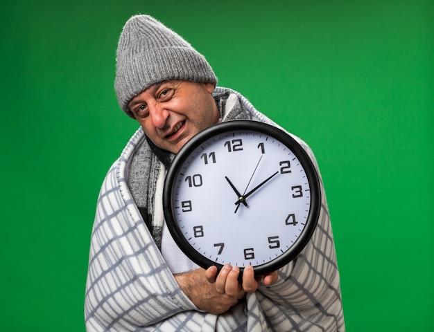 Ansioso sorridente adulto malato uomo caucasico con sciarpa intorno al collo che indossa un cappello invernale avvolto in un plaid tenendo l'orologio isolato sulla parete verde con spazio di copia