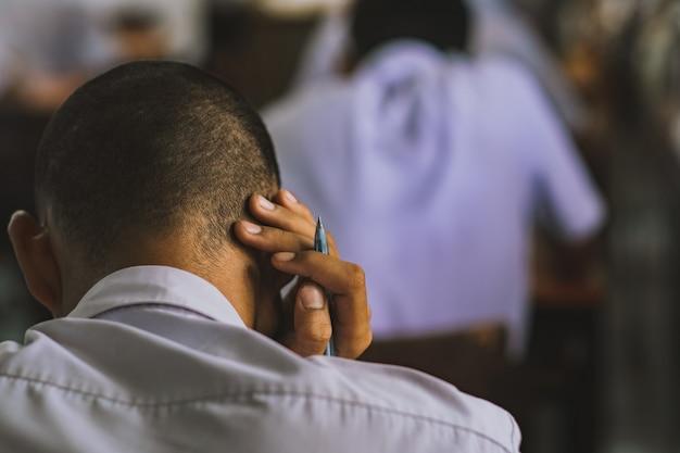 Беспокойный студент сидит и делает экзамен в школе