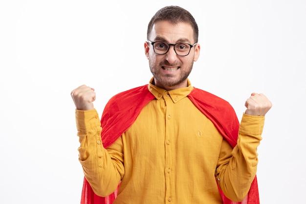 Взволнованный супергерой в оптических очках с красным плащом держит кулаки на белой стене