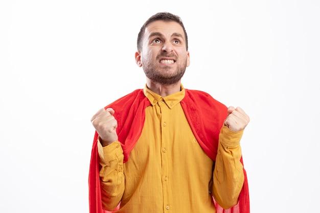 Взволнованный супергерой в красном плаще держит кулаки и смотрит вверх изолированно на белой стене