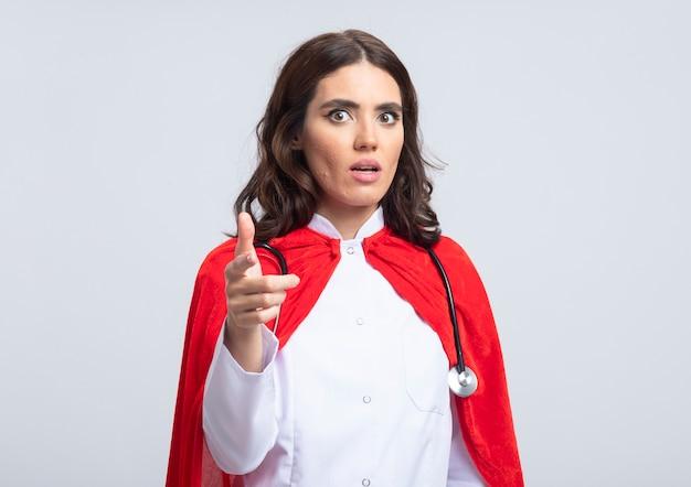 Тревожная суперженщина в униформе доктора с красной накидкой и очками стетоскопа спереди, изолированными на белой стене