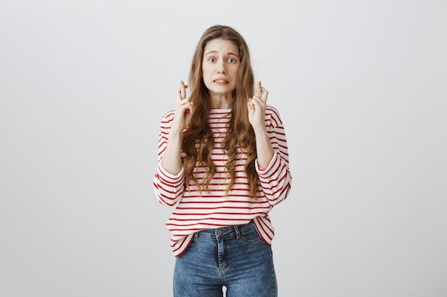 Тревожная девочка-подросток скрестила пальцы, загадывая желание, ожидая хороших новостей
