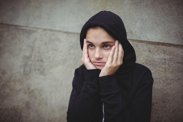顔に手で立っている黒いフード付きジャケットで気になる10代の少女