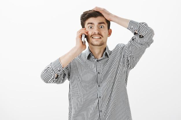 Ragazzo europeo divertente e problematico con barba e baffi, che fa una faccia nervosa colpevole e tiene la mano sulla testa mentre parla sullo smartphone, essendo in ritardo e inventando scuse