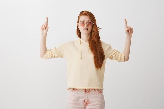 Ansiosa e turbata ragazza dai capelli rossi graziosa che si morde il labbro e punta le dita verso l'alto, guardando preoccupato
