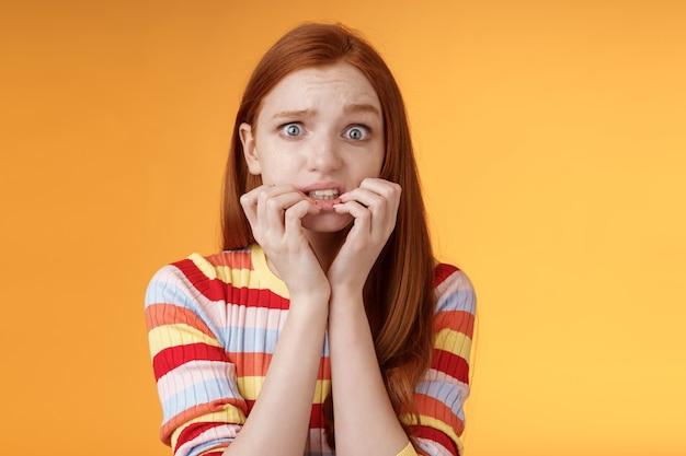 Тревожно неуверенная, робкая, неуверенная в себе рыжая милая девушка волнуется, дрожит от страха, последствия кусает ногти, хмурится, гримасничает испуганно, нервно стоит на оранжевом фоне в ожидании страшного момента.
