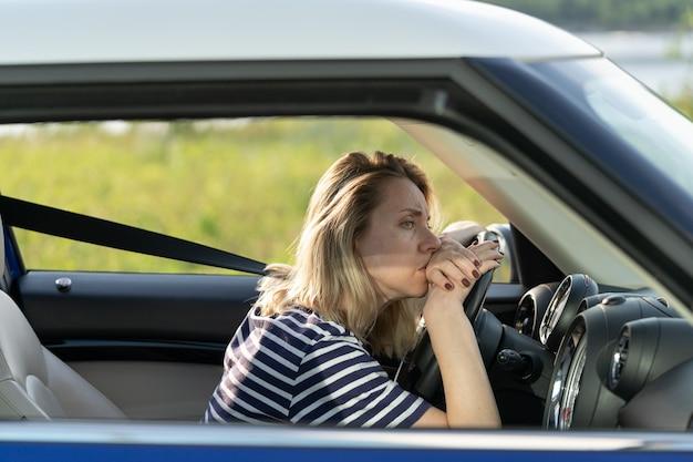 자동차 여성 운전자가 운전하는 것이 두려운 불안 두통으로 고통받는 도로를 바라보는 불안한 화가 여성