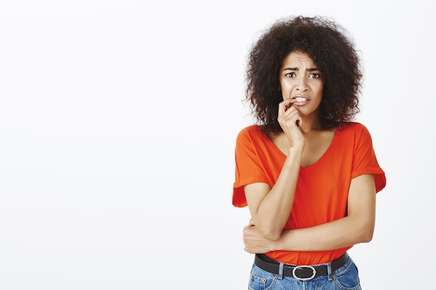 Anxious woman with afro hairstyle posing in the studio