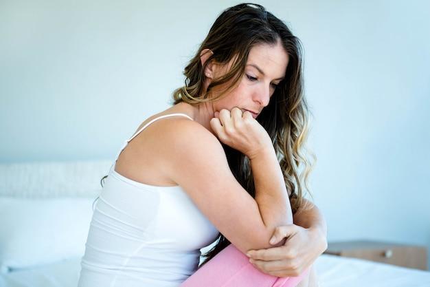 Взволнованная женщина с головой в руках сидит на кровати