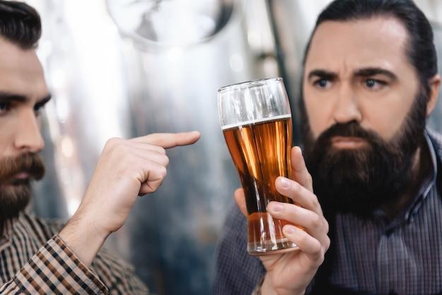 Anxious worried bearded worker test beer color