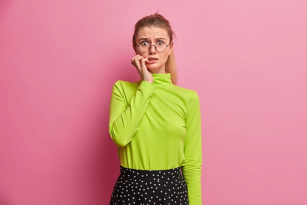 Anxious worried european girl bites finger nails and afraids of something, has big problems, being nervous, wears optical glasses, green turtleneck
