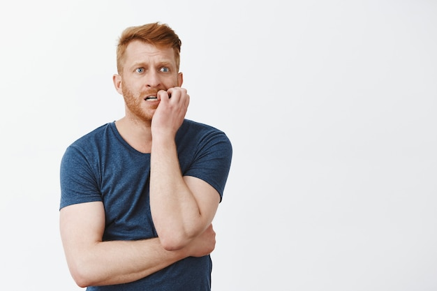 Anxious or worried handsome mature guy with red hair and bristle, biting fingernails nervous and gazing aside, standing over gray wall impatient