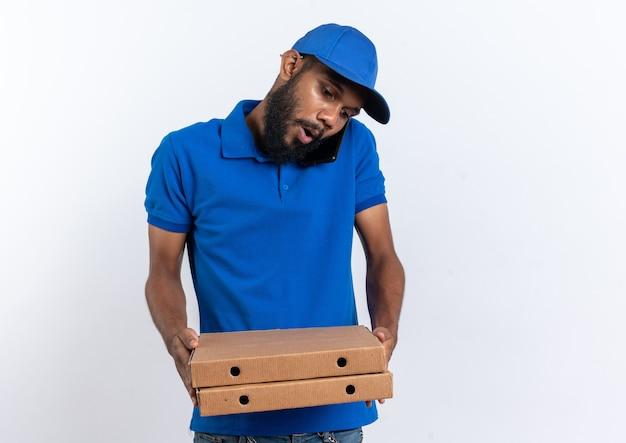 Ansioso giovane fattorino afroamericano che tiene scatole per pizza parlando al telefono isolato su sfondo bianco con spazio di copia